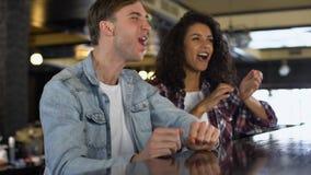 Hombre feliz y mujer que dan el alto cinco, animando para la victoria del equipo de deporte, diversión almacen de metraje de vídeo