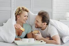 Hombre feliz y mujer que gozan del desayuno en lecho Imagenes de archivo