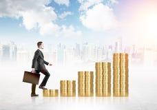 Hombre financiero del crecimiento en monedas Imágenes de archivo libres de regalías