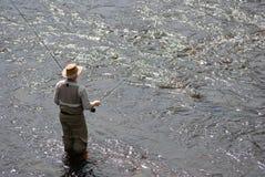 Hombre fly-fishing en el río Foto de archivo