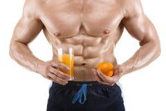 Hombre formado y sano del cuerpo que sostiene un vidrio con el jugo y la naranja, abdominal formada, aislados en blanco Imagen de archivo