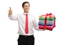 Hombre formalmente vestido con una pila de la ropa planchada y llena m fotos de archivo libres de regalías