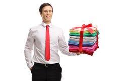 Hombre formalmente vestido con una pila de la ropa planchada y llena w fotografía de archivo
