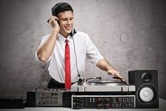 Hombre formalmente vestido que juega música en una placa giratoria fotos de archivo libres de regalías
