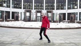 Hombre fresco en danzas rojas de la ropa y de las gafas de sol del deporte al lado de columnas del granito metrajes