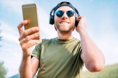 Hombre fresco en gorra de béisbol, auriculares inalámbricos y gafas de sol azules hojeando en su dispositivo del smartphone de la fotos de archivo libres de regalías