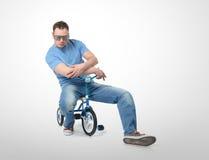 Hombre fresco en vidrios de un encanto en la bicicleta de los niños Imagenes de archivo