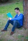 Hombre fresco que lee un libro después un árbol Foto de archivo