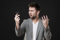Hombre frustrado con el teléfono móvil Imagenes de archivo