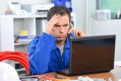 Hombre frustrado en el teléfono que mira el ordenador Fotos de archivo