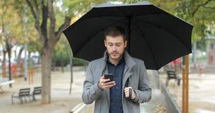 Hombre frustrado que comprueba el app del tiempo en el teléfono en un día lluvioso