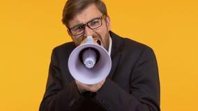 Hombre frustrado que grita en el megáfono que llama a la acción, buscando la ayuda almacen de metraje de vídeo