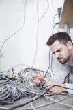 Hombre frustrado que miente abajo intentando imaginar y cables del ordenador de la clase Imagen de archivo
