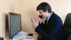 Hombre frustrado que trabaja en el ordenador y que llama el teléfono móvil Compara gráficos en la pantalla y en el papel almacen de video