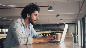 Hombre frustrado usando el ordenador portátil en cafetería almacen de video