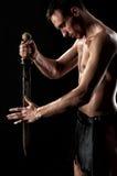 Hombre fuerte con la espada y la armadura antiguas en el fondo negro Fotografía de archivo