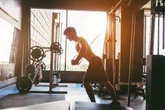 Hombre fuerte de la aptitud que hace ejercicio pesado en la máquina en gimnasio imagen de archivo