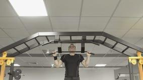 Hombre fuerte del atleta que hace ejercicios en la barra horizontal en gimnasio foto de archivo libre de regalías
