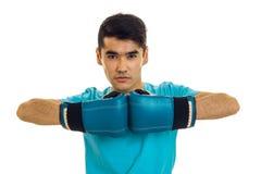 Hombre fuerte joven en el encajonamiento practicante de la camisa azul en los guantes aislados en el fondo blanco Imagen de archivo