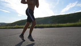 Hombre fuerte joven que corre en el camino en naturaleza hermosa Corredor masculino que activa durante el entrenamiento del entre metrajes