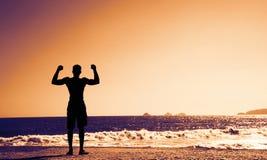 Hombre fuerte que anima en la playa en puesta del sol Fotografía de archivo libre de regalías