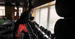 Hombre fuerte que hace ejercicio con pesas de gimnasia almacen de video