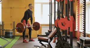 Hombre fuerte que hace ejercicio del arrebatamiento del barbell en el gimnasio metrajes