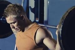 Hombre fuerte que hace posiciones en cuclillas en el gimnasio Imágenes de archivo libres de regalías