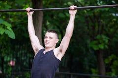 Hombre fuerte que hace tirón-UPS en una barra al aire libre Foto de archivo libre de regalías
