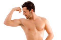 Hombre fuerte que mira sus músculos Fotos de archivo libres de regalías
