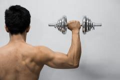 Hombre fuerte que se resuelve con pesa de gimnasia imagen de archivo