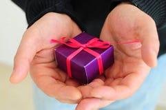Hombre gifting el pequeño presente Fotos de archivo