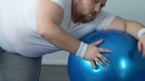 Hombre gordo agotado que cae abajo en piso con la bola de la aptitud, falta de energía del deporte metrajes