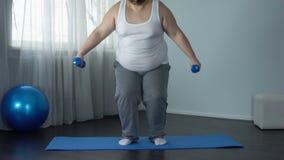 Hombre gordo agotado que se sienta en el piso con pesas de gimnasia, programa fastidioso del entrenamiento, deporte almacen de metraje de vídeo
