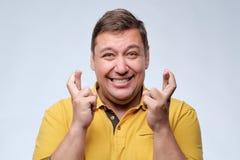 Hombre gordo atractivo en el momento especial que espera de la camiseta amarilla para y fingeres que cruzan Imágenes de archivo libres de regalías