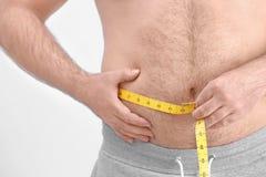 Hombre gordo con la cinta métrica Imagen de archivo libre de regalías