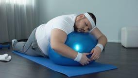 Hombre gordo con poca fuerza de voluntad que se relaja en la bola de la aptitud, rotura casera del entrenamiento, holgazanería almacen de video