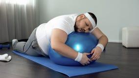 Hombre gordo con poca fuerza de voluntad que se relaja en la bola de la aptitud, rotura casera del entrenamiento, holgazanería fotos de archivo