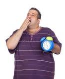 Hombre gordo con un reloj de alarma azul que bosteza Foto de archivo