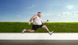 Hombre gordo divertido en el funcionamiento foto de archivo