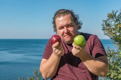 Hombre gordo divertido en el océano que come las frutas Vacaciones, pérdida de peso y consumición sana foto de archivo
