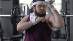 Hombre gordo divertido en gimnasio que finge tener músculos fuertes, atrayendo la atención almacen de video