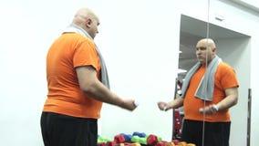 Hombre gordo divertido que comienza a coger las pesas de gimnasia más pequeñas