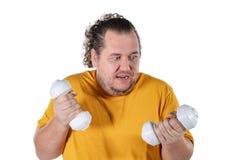 Hombre gordo divertido que ejercita con pesas de gimnasia y que mira la cámara aislada en el fondo blanco foto de archivo libre de regalías