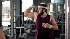 Hombre gordo divertido que mira el gimnasio de la reflexión de espejo y que presenta, fingimiento muscular foto de archivo