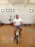 Hombre gordo en el simulador de la bici Fotografía de archivo libre de regalías