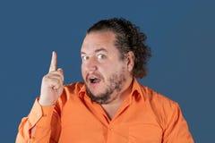 Hombre gordo en la camisa anaranjada que detiene su pulgar Él tenía una gran idea fotos de archivo libres de regalías