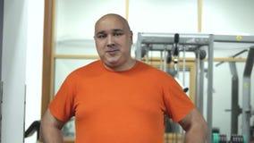 Hombre gordo en un gimnasio en la camiseta anaranjada que se coloca y que mira feliz a la leva