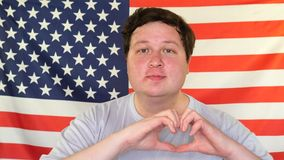 Hombre gordo feliz en el amor que hace el coraz?n con los fingeres y que sonr?e en el fondo de una bandera de los E.E.U.U. metrajes