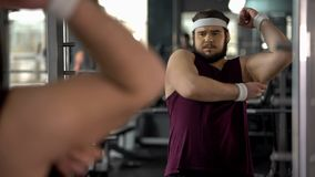 Hombre gordo frustrado que mira su grasa de la mano que sueña sobre el bíceps, obesidad fotografía de archivo